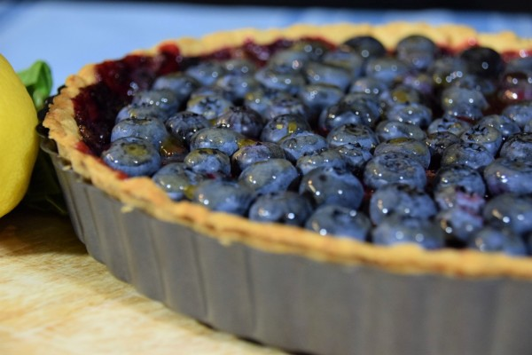 Stardew Valley Blueberry Tart in pan with basil and lemon