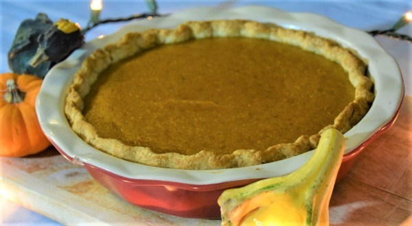 Pumpkin pie in a red pie plate surrounded by multicolored gourds and fairy lights