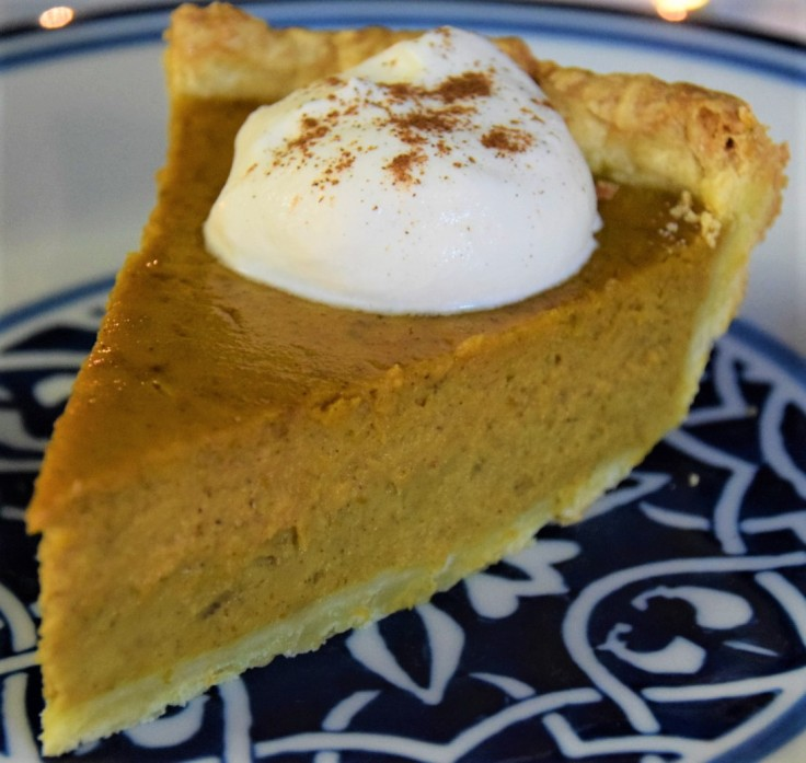 Slice of pumpkin pie with a dollop of whipped cream on a blue and white plate