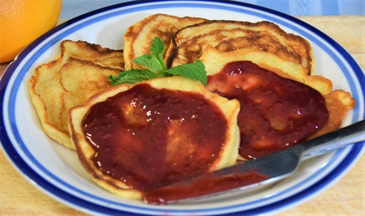 Small stack of cheese pancakes topped with fruit preserves and garnished with mint on a plate