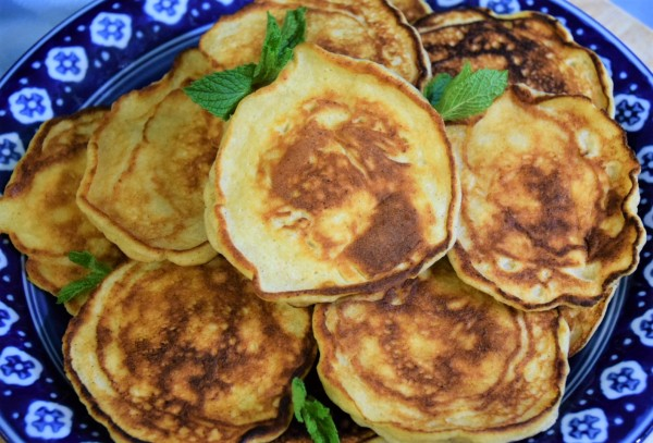 Pile of cheese pancakes on blue and white plate garnished with mint