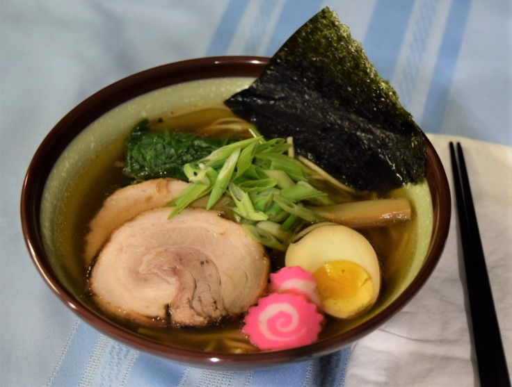 bowl of shoyu soy ramen with toppings chashu pork, naurtomaki or kamaboko, egg, menma, scallions, spinach, and nori