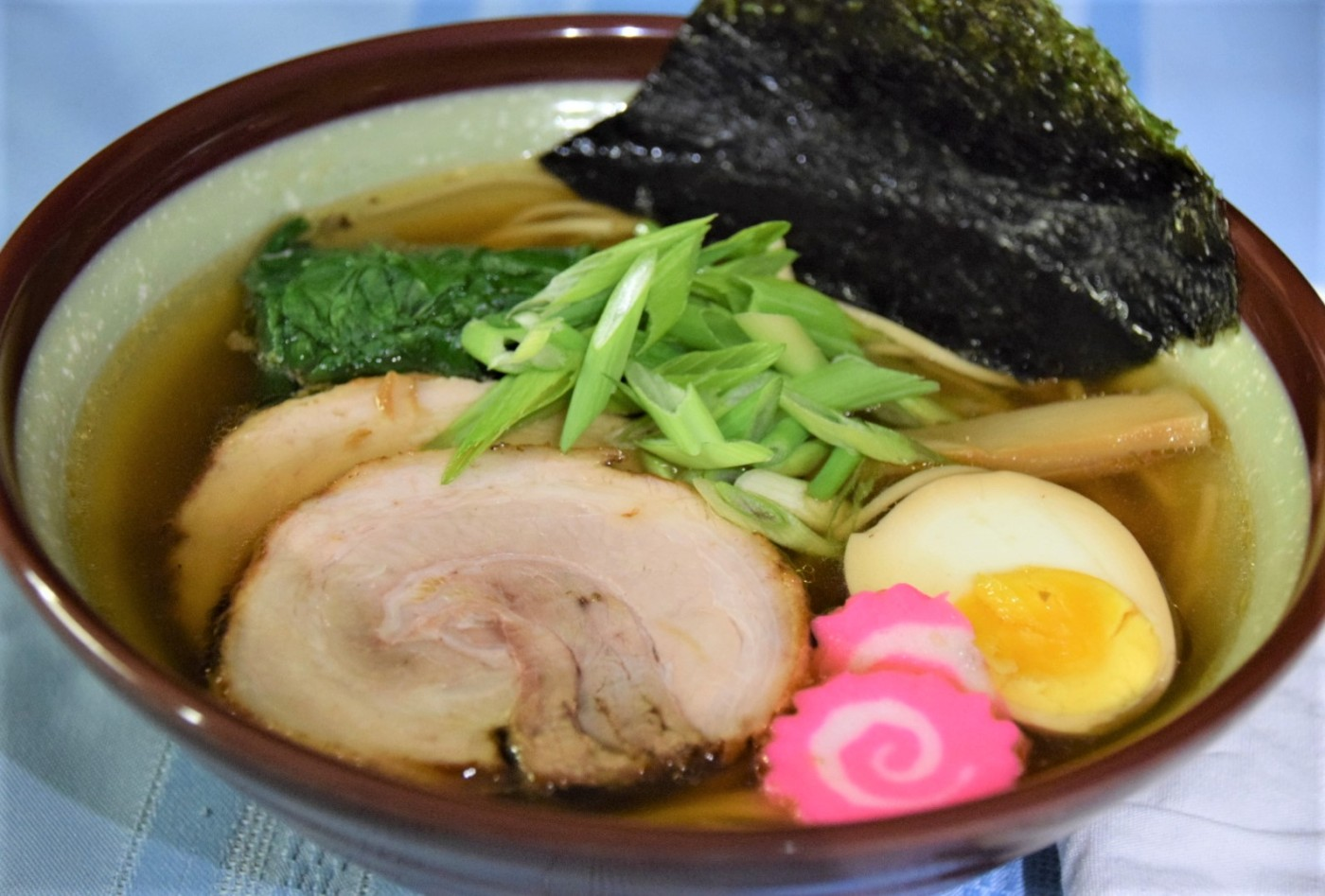 bowl of shoyu soy ramen with chashu, menma, narutomaki, egg, nori, spinach, and scallions