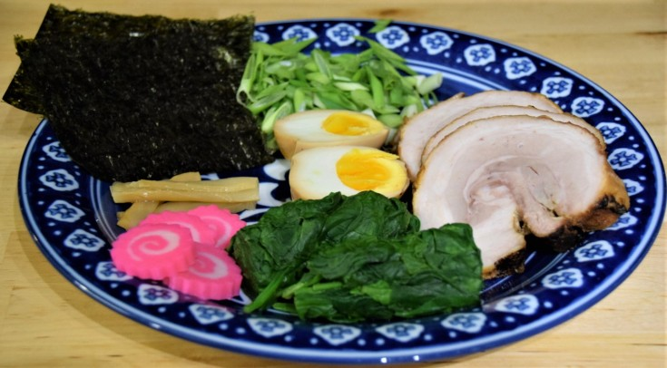 ramen toppings on a blue and white plate menma chashu pork egg ajitsuke tamago scallions nori menma narutomaki kamaboko spinach