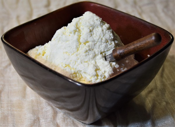 Pyramid of homemade ricotta in a dark square bowl