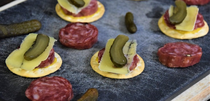 A black cutting board covered in salami, pickles, and crackers topped with mustard, salami slices, cheese, and sliced pickles