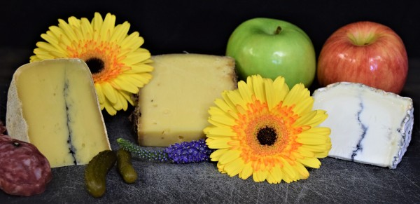 Three cheese wedges in a row surrounded by fruits, flowers, and food