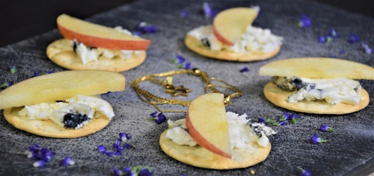 Crackers topped with white and black cheese and apple slices, circling a star necklace, surrounded by purple flower petals, all on a black background.