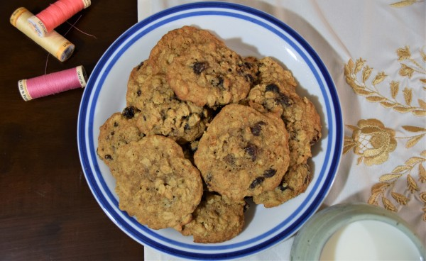 oatmeal raisin cookies on a white and blue plate surrounded by thread spools, a white and gold cloth, a wood background, and a blue mug of milk