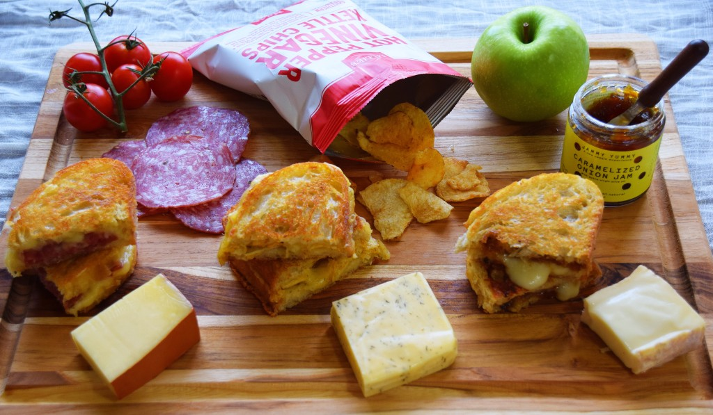 A grilled cheese themed cheese board, with three different grilled cheeses and three pale cheeses towards the bottom, a jar of onion jam and a green apple in the top right, a white and red bag of spicy chips in the top middle, and a cluster of cherry cherry tomatoes and salami in the top left.
