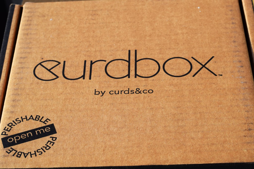 """A light brown box that says """"Curdbox"""" in fancy black letters; underneath it says """"by curds&co"""". The bottom left corner text says """"Perishable open me."""""""