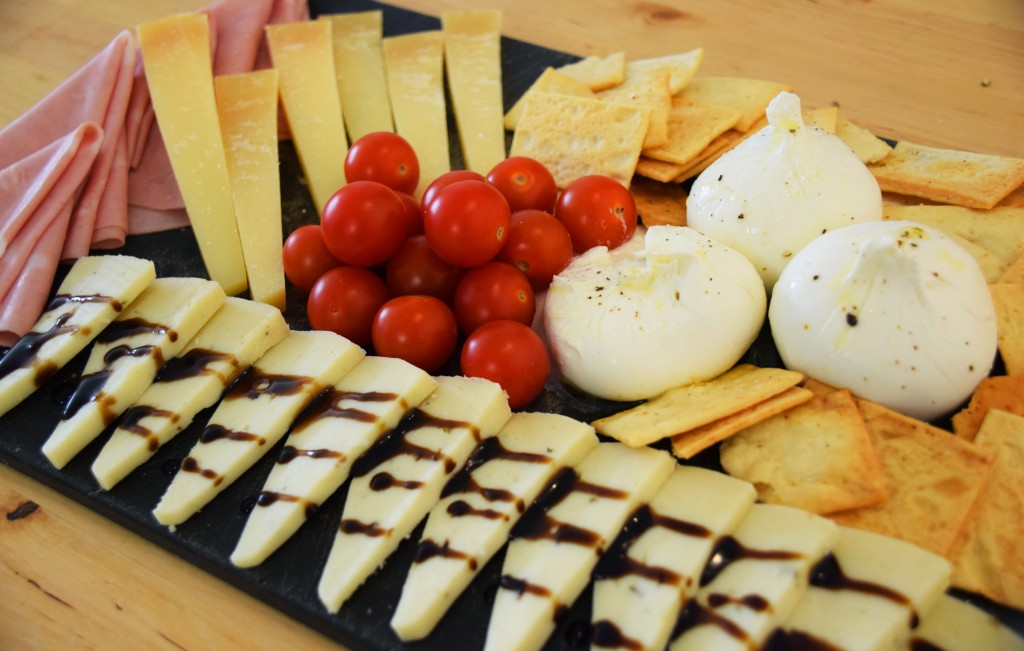 An Italian-themed cheese board with pouches of white mozzarella, tan garlic crisps, little red cherry tomatoes, triangles of tan cheese on top of triangles of pink mortadella, and triangles of cream-colored cheese in a row at the bottom. The bottom cheese is drizzled with a blackish balsamic vinegar.