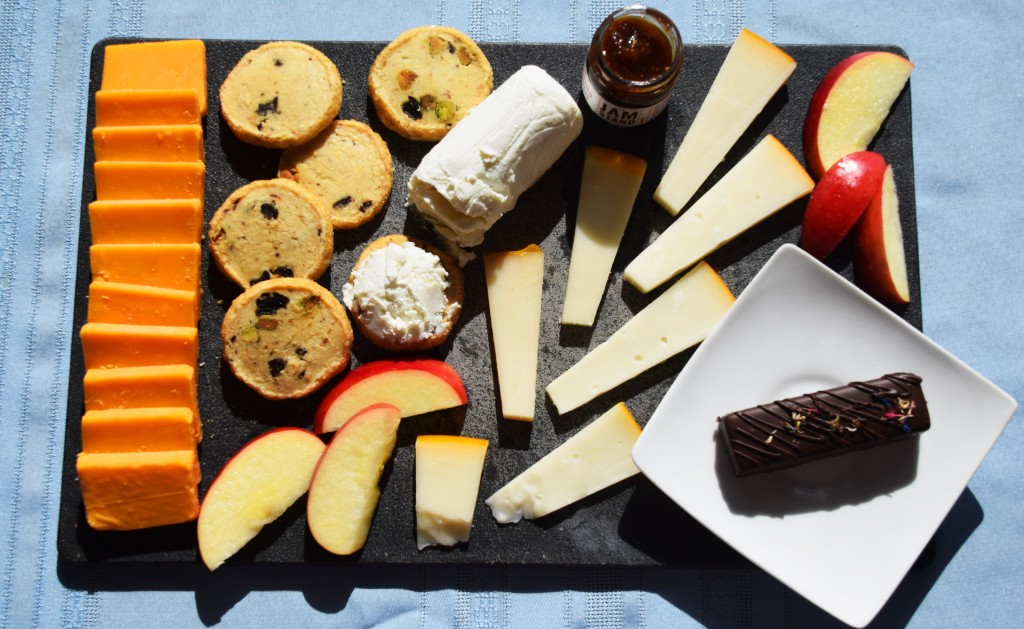 A black cheese board on a light blue background, covered by squares of orange cheddar on the left, cherry pistachio cookies, apple slices, and triangles of white gouda in the middle, a log of white goat cheese, a small jar of dark purple jam, and in the bottom right corner a white plate with a rectangular chocolate bar on it.